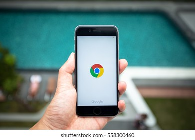 Bangkok, Thailand - Jan 18,2016:Chrome app on the Apple iPhone display screen. Top view of Business workplace.Closeup on a man's hands as he is using a smart phone