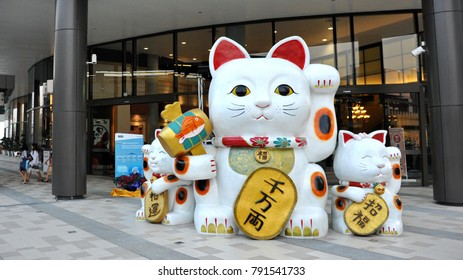 Bangkok, Thailand - Jan 22, 2013: A large Asian style beckoning cat sculpture greets customers at the Gateway Ekamai shopping mall. The Asian themed mall is popular with Japanese expats and locals.