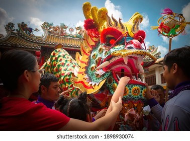 BANGKOK, THAILAND - JAN 25 2020: People give money through dragon mouth for lucky, wealthy and happiness in Chinese New Year Festival at Chinatown, Yaowarat. Traditional dragon dance parade at shrine.