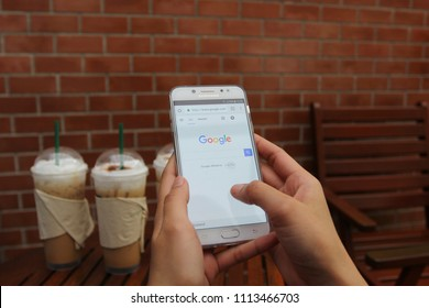 Bangkok, Thailand : Jane 13, 2018, Woman hand using Samsung galaxy J7 Plus with Google search home page in coffee shop, typing message or checking newsfeed on social networks