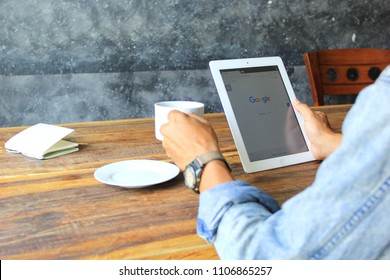 Bangkok, Thailand : Jane 3, 2018, Man hand using ipad smart device with Google search home page and hand holding cup of coffee in home office, typing message or checking newsfeed on social networks