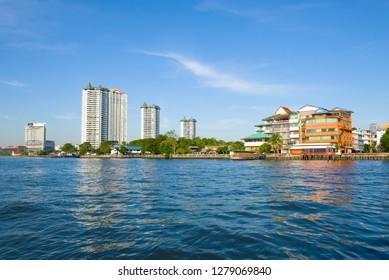 BANGKOK, THAILAND - JANUARY 01, 2019: Sunny day on the Chao Phraya River. Outskirts of modern Bangkok