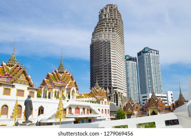 BANGKOK, THAILAND - JANUARY 02, 2019: View of the abandoned skyscraper of Sathorn Unique Tower from the Buddhist temple Wat Yannava