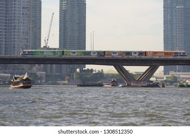 "BANGKOK, THAILAND - JANUARY 02, 2019: The train of the ""BTS SkyTrain""  land subway on the bridge through Chao Phraya River river"