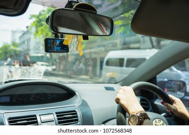 BANGKOK, THAILAND - JANUARY 06 2018:  hand of women driving and Front view camera for car camcorder on street in BANGKOK . THAILAND