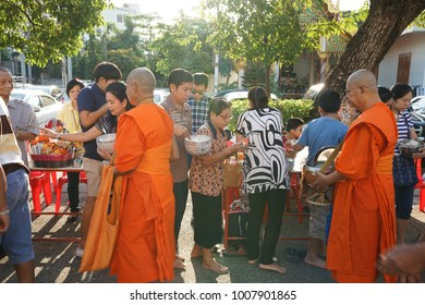 BANGKOK, THAILAND - January 1, 2018: People make merit by offering food to monk at the temple.