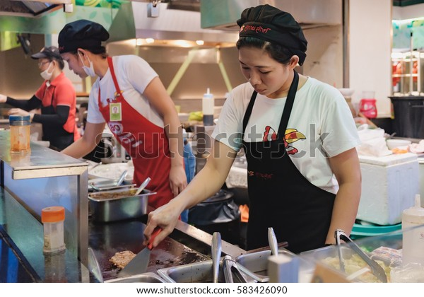 Bangkok, Thailand - January 10, 2016: Thai woman cooking at Food Park in Big C Supercenter on Ratchadamri Road, Bangkok, Thailand. There are food courts that provide International or Thai dishes