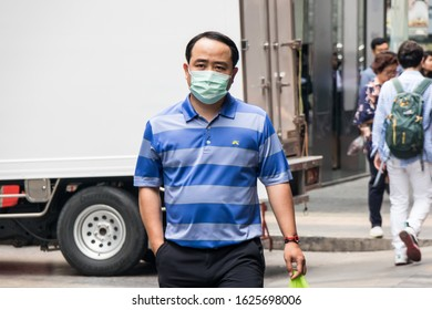 Bangkok, Thailand - January 10th 2020: Man wearing a mask to protect against both smog and coronavirus. The city has been plagued with smog in recent imes and cases of coronavirus have been reported.