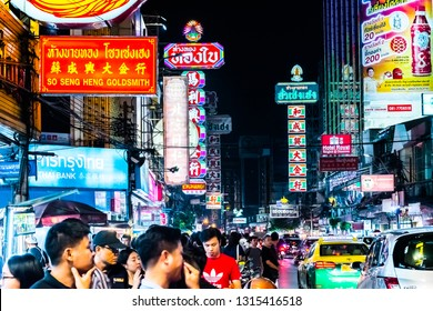 BANGKOK, THAILAND - JANUARY 12, 2018: Traffic on Yaowarat Road passes below lit signs in the Chinatown district at dusk