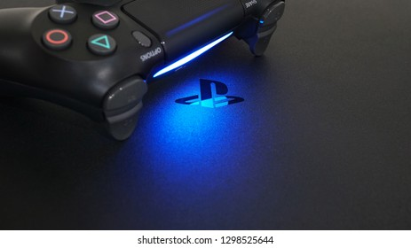 Bangkok Thailand - January 13, 2019: Sony PlayStation 4 Slim (PS4) with DualShock 4 controller shining blue LED on logo, Home video game console developed by Sony Interactive Entertainment