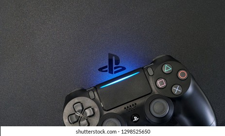 Bangkok Thailand - January 13, 2019: Sony PlayStation 4 Slim (PS4) with DualShock 4 controller shining blue LED on logo, Home video game console developed by Sony Interactive Entertainment, Top view
