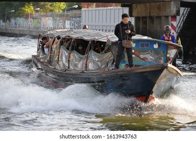 Bangkok, Thailand - January 13 2020: Passenger boat ticket salesman in Khlong Saen Saeb will pick up the phone to play without fearing to fall into the water