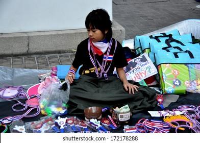 Bangkok, Thailand January 14, 2014:  Woman selling Operation Shut Down Bangkok souvenirs sitting on Sukhamvit Road at Asok