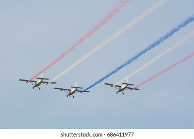 Bangkok , Thailand - January 14 , 2017. Royal Thai Air Force AU-23A peacemaker utility aircraft flying in 3 ship formation performing national flag smoke trail in national children's day.