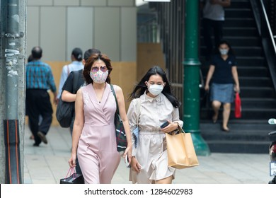 Bangkok, Thailand - January 14, 2019 :Unidentified woman wearing mouth mask against air smog pollution with PM 2.5 walking on sidewalk in Bangkok city, Thailand.