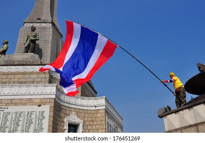 Bangkok, Thailand - January 16, 2014:  Protestor waving a giant Thai flag standing on the Victory Monument during the Shut Down Bangkok demonstrations  *