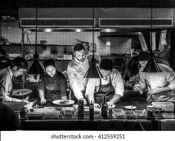 BANGKOK, THAILAND - January 16, 2016: Head chef coaches his team in a busy Italian Tuscan kitchen. Kitchen Display Systems (KDS) in back of the house (BOH) operations
