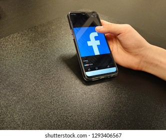 Bangkok, Thailand. January 16, 2019 - hand holding smartphone with facebook application on screen. mobile phone on black table background and copy space.