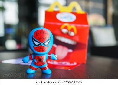BANGKOK, THAILAND - JANUARY 19, 2019 : spiderman toy with blurred Happy Meal box in front of Mcdonald's restaurant