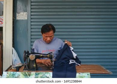 BANGKOK, THAILAND - JANUARY 20, 2019: Asian elder man sewing clothes at his portable tailor service in local market