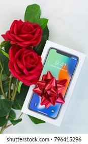 BANGKOK, THAILAND - JANUARY 2018 : Box of new iPhone X (iPhone 10) with top view of red ribbon and red roses as a gift on marble background on January 16, 2018 in Bangkok, Thailand