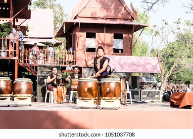 BANGKOK, THAILAND - JANUARY 2018: People and tourist enjoying watching Thai musicians are playing Thai music on the stage in the Thai cultural heritage. Thai traditional house architecture background.