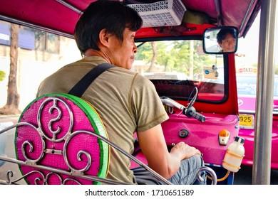 Bangkok, Thailand - January, 2020: A beautiful view of Tuk Tuk driver. Pink Tuk-tuk driver on road of Bangkok.