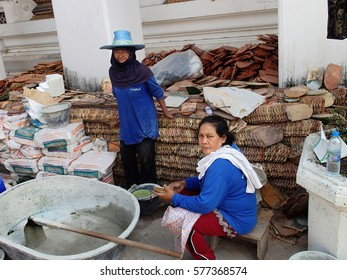 BANGKOK, THAILAND - JANUARY 20,2013: Women repairing an ancient temple in the monastery Wat Pho