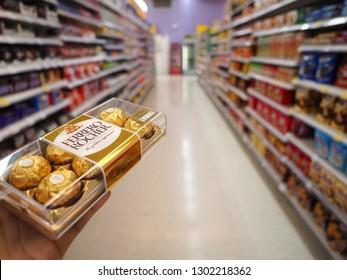 BANGKOK, THAILAND - JANUARY 20,2019 : Hand holds Ferrero Rocher premium chocolate, Ferrero Rocher is a spherical chocolate produced by the Italian chocolatier Ferrero SpA, Shopping concept.