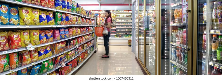 BANGKOK, THAILAND - JANUARY 22: An unidentified woman shops in the potato chips section of 7-Eleven convenient store in Bangkok on January 22, 2018.