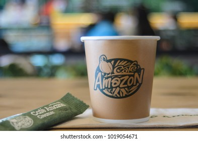 BANGKOK, THAILAND - JANUARY 25, 2018: Cup of coffee on wooden table in Cafe Amazon service store.Thailand Coffee shops, this brand has more than1,800 branch in this year.