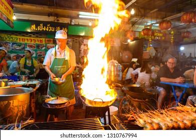 Bangkok, Thailand - January 26, 2019 : Street food chef cooking with fire at Yaowarat road in Bangkok