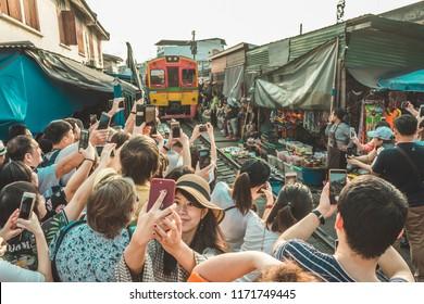 Bangkok, Thailand - January 27, 2018: Tourists waiting for the train and taking photos at Maeklong railroad track market (Train Market).