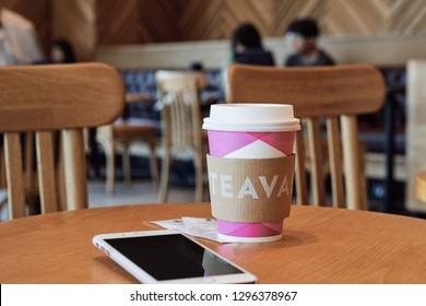 BANGKOK, THAILAND - January 27, 2019: Starbucks coffee cup on the table with smartphone in coffeshop