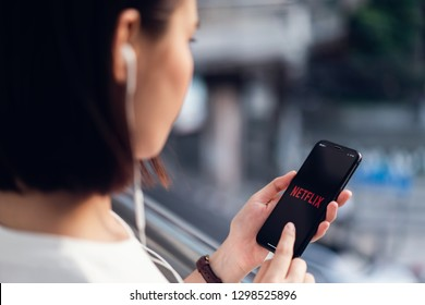 Bangkok, Thailand - January 29, 2019 : women use Netflix app on smart phone screen. Netflix is an international leading subscription service for watching TV episodes and movies.