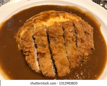 BANGKOK, Thailand - January 29, 2019: Omelette curry with pork cutlet (katsu) on white plate