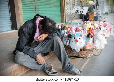 Bangkok, Thailand - January, 30, 2011: A hawker sleeps on a city centre street.