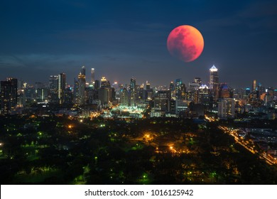 BANGKOK, THAILAND - January 31, 2018 : Lunar eclipse, Super blue blood moon taken from top of a building, It is a wonderful natural phenomenon with a city view of Lumphini Park and modern building.