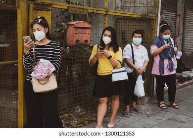 Bangkok, Thailand - January 31, 2019:Unidentified people wearing mouth mask against air smog pollution with PM 2.5 using cellphone and waiting bus public on sidewalk at chatuchak district in Bangkok