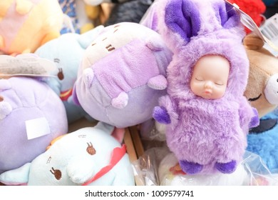 Bangkok, Thailand - January 6, 2018 : A pile of Disney plush toys with selective focus on a sleeping baby in fluffy bunny suit and other Disney characters on the background such as Eeyore and Dumbo.