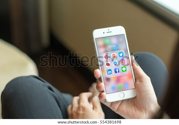 Bangkok, THAILAND - January 8th, 2017: Woman lifestyle relaxing using smartphone with icons of social media on screen, smart phone life style, mobile phone era in everyday life