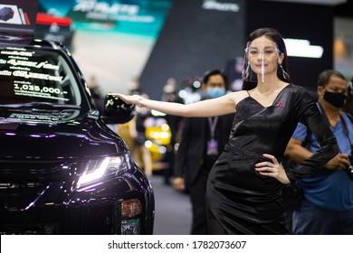 Bangkok, Thailand, Jul 15, 2020 - Asian pretty model standing by the Mitsubishi pickup truck in Bangkok Motor Show 2020, Motor show pretty model with face shield during the Covid-19 virus spreading