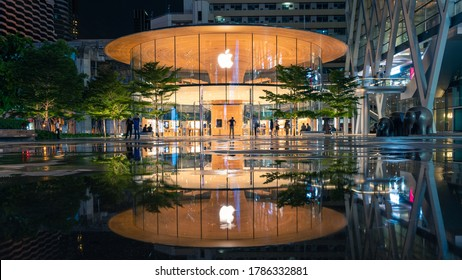 Bangkok / Thailand - Jul 28 2020: Night view of Apple Store (Apple Central World), the new flagship store in central business district of Bangkok Thailand with reflection after raining