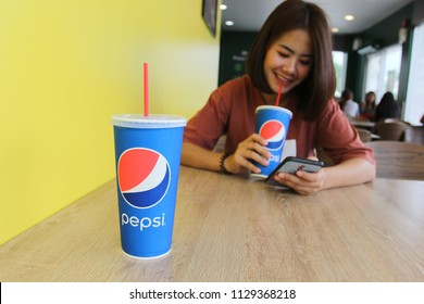 Bangkok, Thailand : July 07,2018: Drink produced by PepsiCo on the wooden table and young woman drink pepsi in restaurant