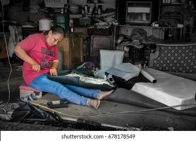 BANGKOK, THAILAND - July 1: Underpaid low income migrant worker fixes a motorcycle seat. Due to lack of labor protection, women make up almost 40% of migrant workers in Thailand.