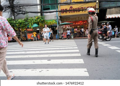 Bangkok, Thailand - July 10, 2019: A Police man controlling the traffic in Chinatown Bangkok. Chinatown now covers a large area around Yaowarat and Charoen Krung Road and it is crowded everyday.