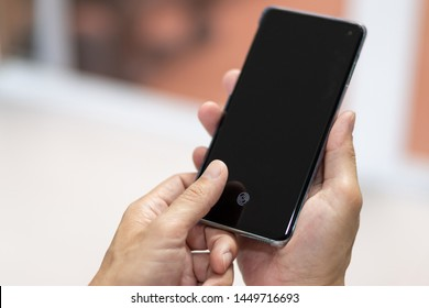 Bangkok / Thailand- July 13 2019: Hands holding New Samsung Galaxy S10 with new app of fingerprint scan on smartphone screen to unlock phone.