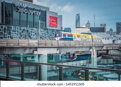 BANGKOK, THAILAND - JULY 13, 2019 : An exterior view of Siam Discovery with BTS skytrain passing. Siam Discovery is one of Bangkok's main shopping areas.