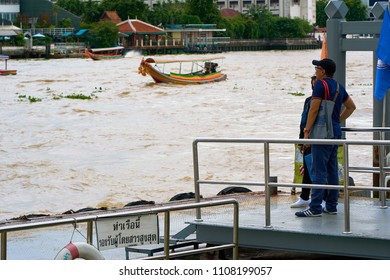 BANGKOK, THAILAND - July 14, 2017: Tourists waiting for boat at Chao Phraya river metal pier with traditional longtail boat in background.