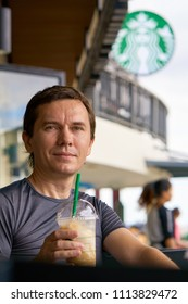 BANGKOK, THAILAND - JULY 14, 2017: Caucasian tourist is sitting and relaxing in outdoor part of Starbucks coffee shop located on Tha Maharaj Pier. Illustrative editorial.